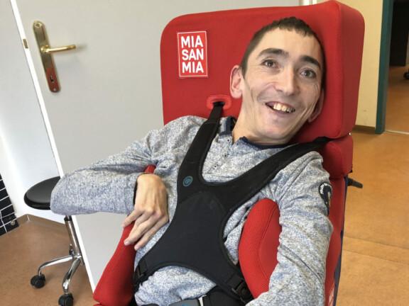 Michael Aigner sitzt in einer Rollstuhl-Sitzschale im FC Bayern Design