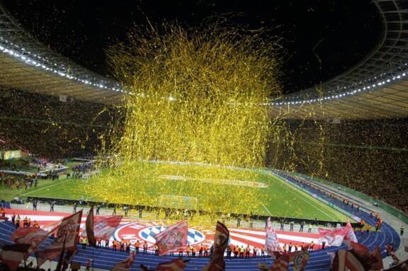 Goldenes Lametta und viele Bayern-Fahnen in der Kurve mit Blick aufs Spielfeld
