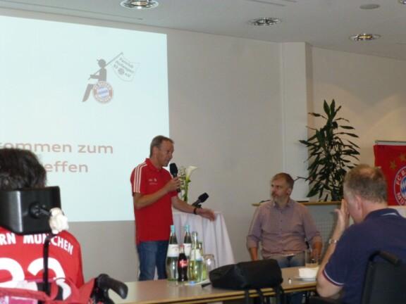 Bertl Russer im roten FC Bayerntrikot sprich in Mikrofon zu Publikum