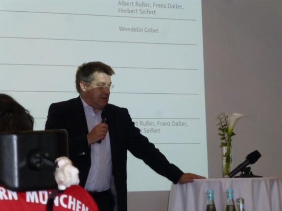 Bernhard Karst steht mit einem Mikrofon vor der Leinwand