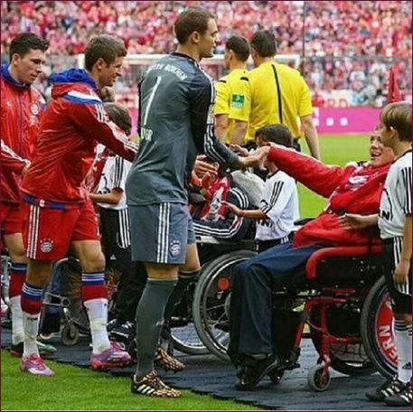 Rollstuhlfahrer werden auf dem Spielfeld von den Spielern begrüßt