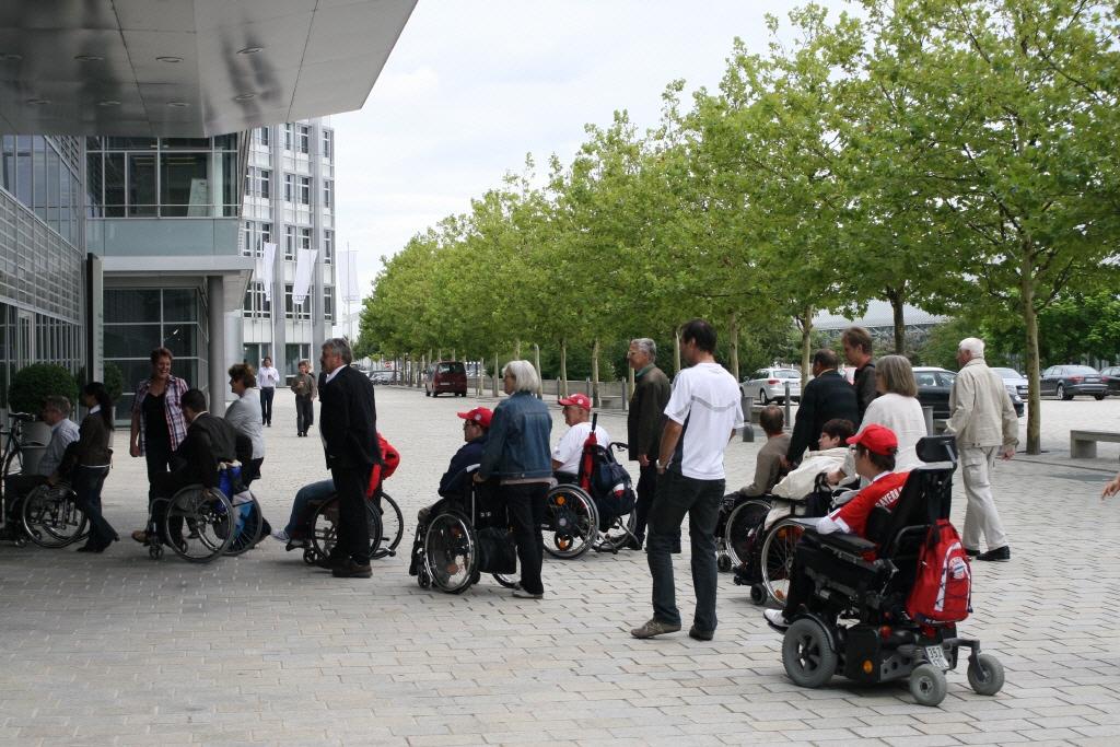Rollstuhlfahrer in der Warteschlange zum Eingang am Audi-Forum
