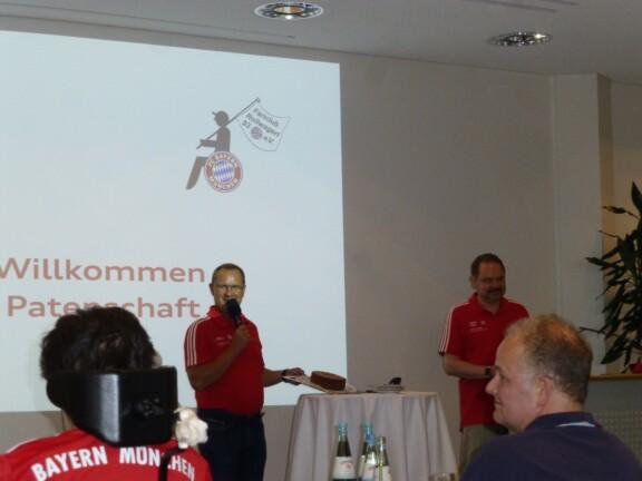 Franz Daller und Herbert Seifert stehen mit einem Mikrofon vor der Leinwand