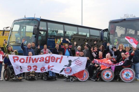 Gruppenfoto mit Banner vor den zwei barrierefreien Reisebussen