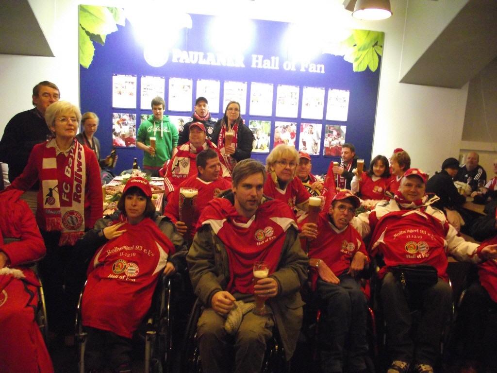 Gruppenfoto der Rollwagerl Mitglieder im Paulaner Fantreff vor der Paulaner Hall of Fan Wand