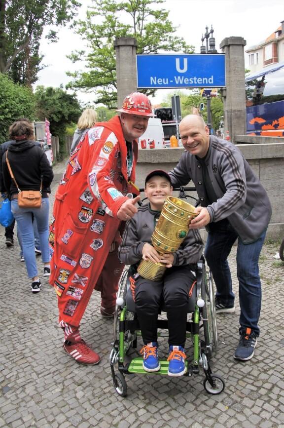 Rollwagerl-Mitglied Maximilian Böhme mit Pokal und sein Vater Kai Zeumer vor der U-Bahn-Station Neu-Westend