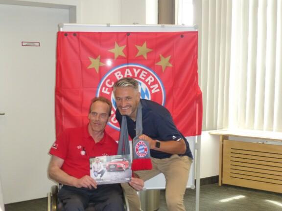 Gerd Schönfelder und ein Bayern Fan im Rollstuhl posieren für ein Foto