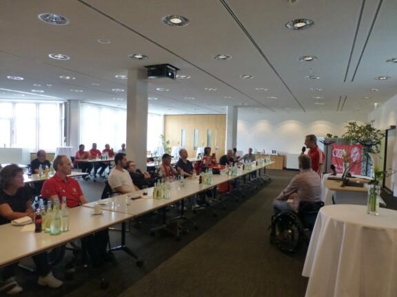 Bertl Russer und Kim Krämer stehen vor Publikum an langen Tischreihen