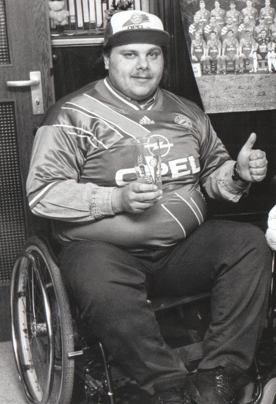 Thomas Winkler, Gründer des Rollwagerl 93 eV, lächelnd, im Rollstuhl, mit Bayern-Cappy und Bayern-Trikot, in der rechten Hand ein Bayern-Trinkglas, den Daumen der linken Hand nach oben.
