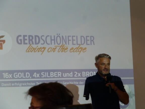 Gerd Schönfelder steht mit einem Mikrofon vor der Leinwand auf der steht Gerd Schönefelder und darunter living on the edge