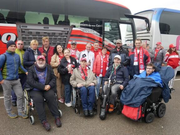 Bayern-Fans mit und ohne Rollstuhl vor einem Bus