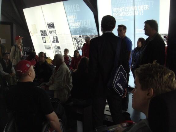 Rollifahrer im Museum vor einer Infowand über Krieg und Frieden;