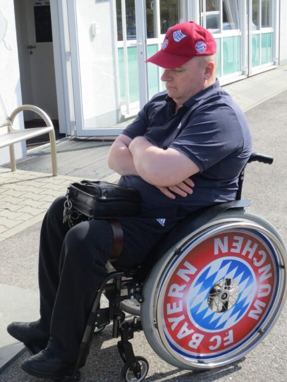 Uli trägt eine Bayern-Cappi und schläft im Rollstuhl mit Bayern-Logo