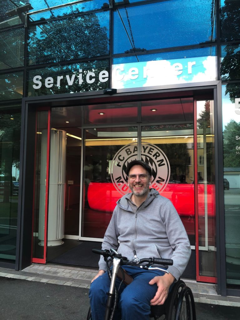 Kim Krämer im Rollstuhl vor dem FC Bayern Service Center