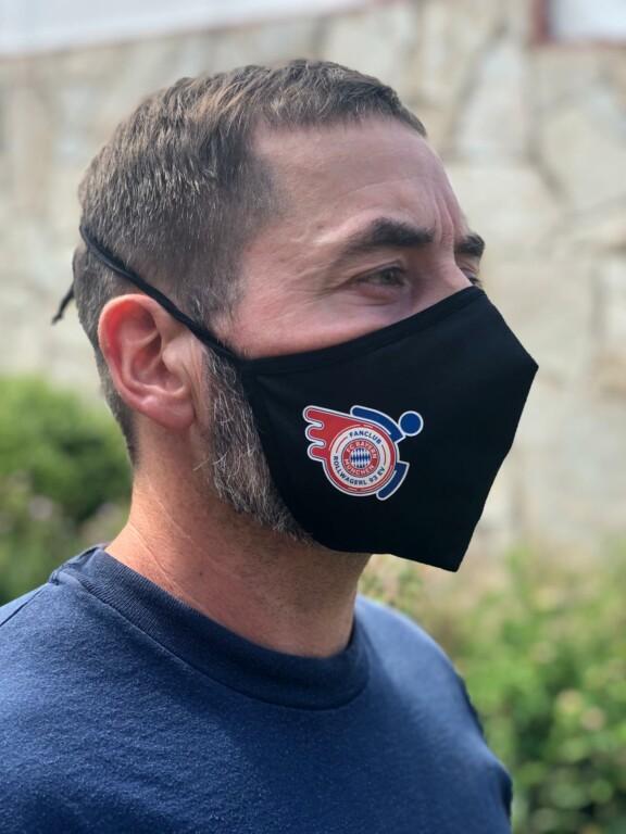 Mann mit Mund-Nasenschutz mit Rollwagerl-Logo in schwarz