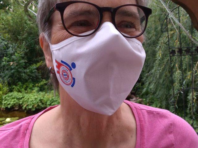 Frau mit Mund-Nasenschutz mit Rollwagerl-Logo in weiß