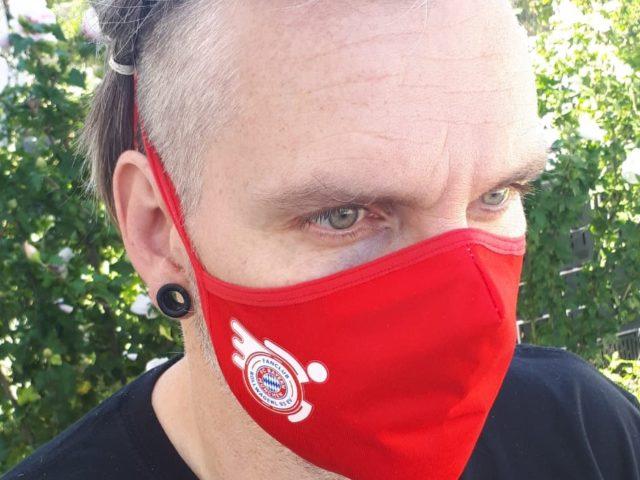 Mann mit Mund-Nasenschutz mit Rollwagerl-Logo in rot