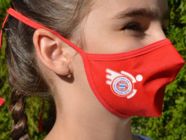 Kind mit Mund-Nasenschutz mit Rollwagerl-Logo in rot