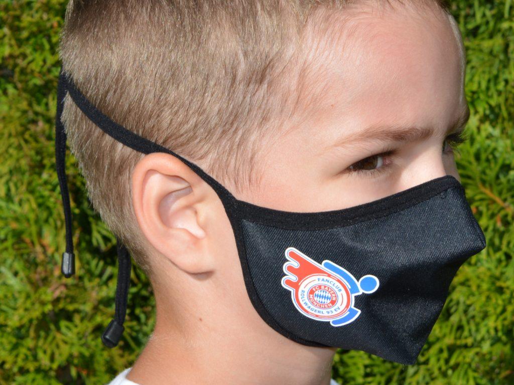 Kind mit Mund-Nasenschutz mit Rollwagerl-Logo in schwarz