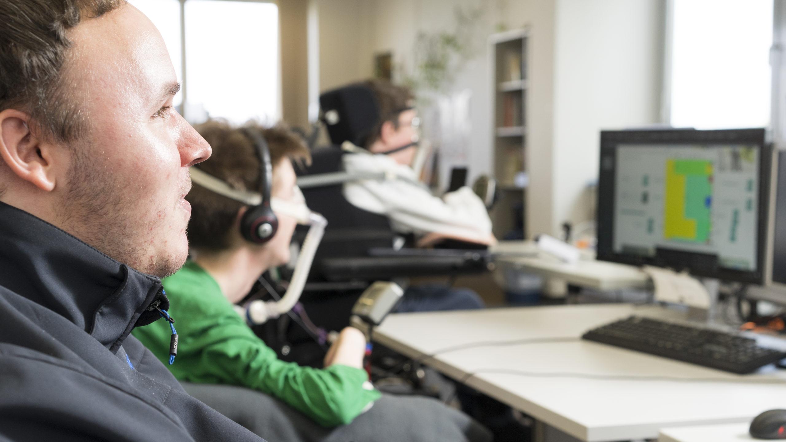 Drei körperbehinderte Männer an ihrem PC-Arbeitsplatz