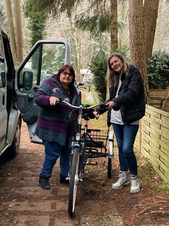 Zwei Frauen stehen neben einem E-Dreirad
