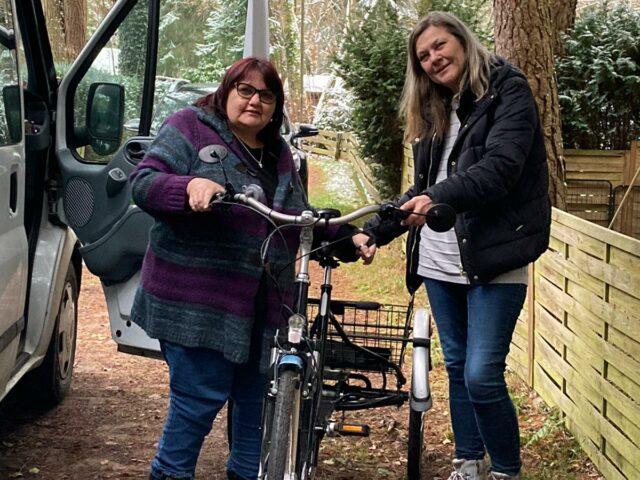 Frau Zagar und Frau Ziegelmüller stehen an einem Bus in der Mitte steht ein Elektro-Dreirad
