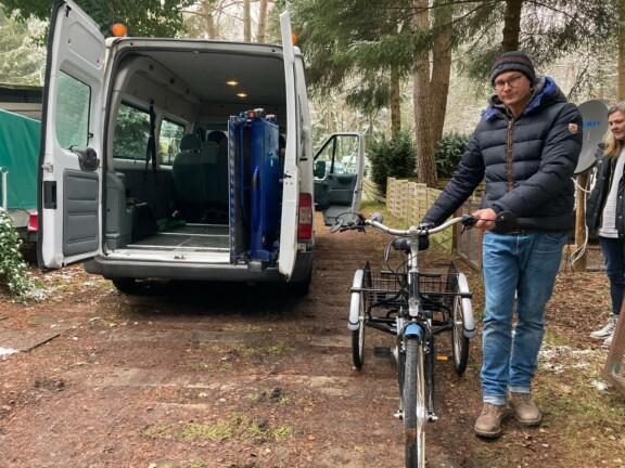 Mann steht neben einem E-Dreirad neben einem offenen Kleinbus
