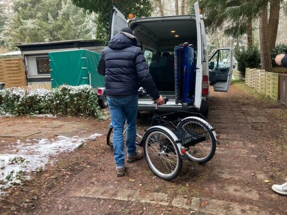Mann beginnt ein E-Dreirad in einen Kleinbus zu verladen