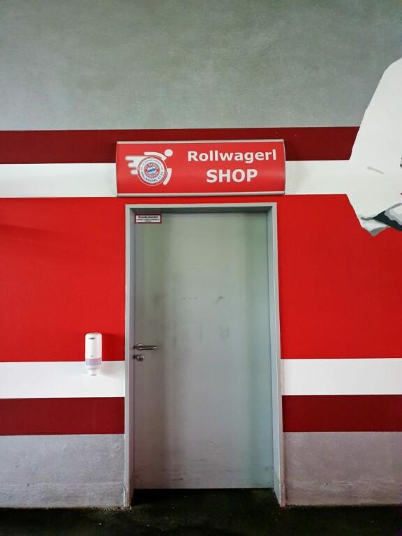 Rollwagerl-SHOP Schild bei Tag über der Tür in der Allianz Arena.