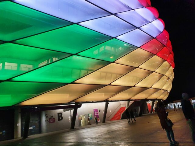 Die Allianz Arena in bunter Farbe bei Nacht und in Nahaufnahme.