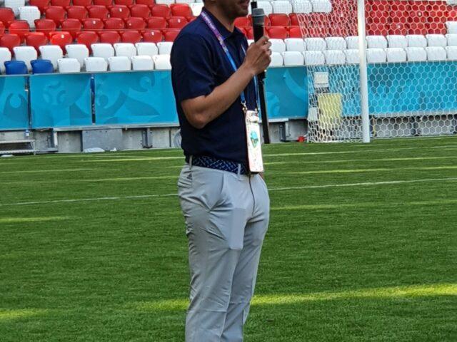 Philipp Lahm spricht n ein Mikrofon und steht dabei auf dem Rasen der Allianz Arena.