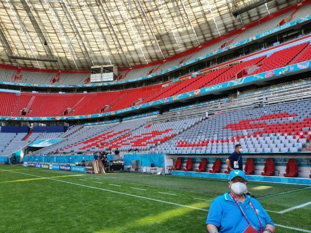 Monika steht auf dem Rasen der Allianz Arena. Im Hintergrund ist die Trainerbank zu sehen.