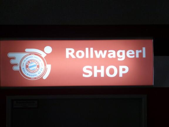 Rollwagerl-SHOP Schild über der Eingangstür des Rollwagerl-SHOP in der Allianz Arena beleuchtet bei Nacht.