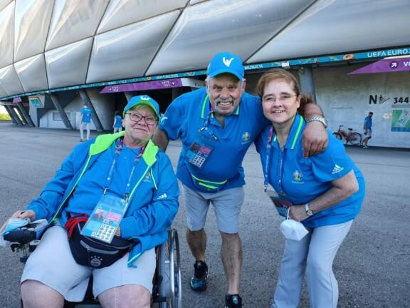 Drei Volunteers vor der Allianz Arena, eine Frau im Rollstuhl und zwei Fußgänger*innen
