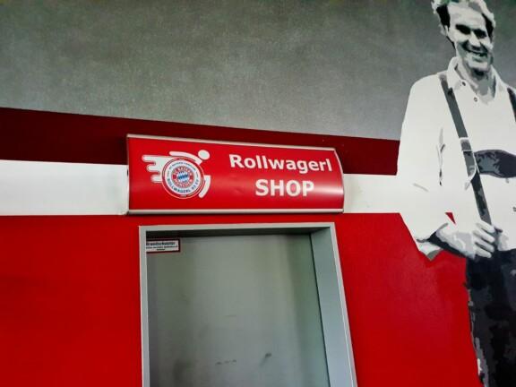 Rollwagerl-SHOP Schild in der Allianz Arena über der Tür zum SHOP. Daneben ein Bild an der Wand von Rummenigge.