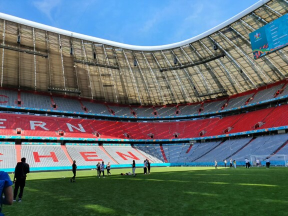 Menschen stehen auf dem Rasen der leeren Allianz-Arena