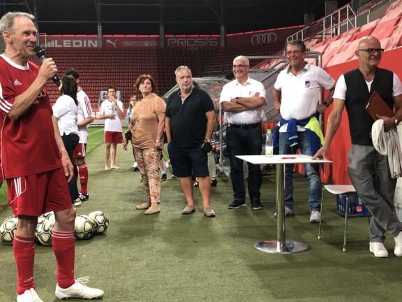 Ein Mann im Fußball Trikot spricht ins Mikrofon. Fünf Menschen stehen daneben. Es ist in einem Stadion.