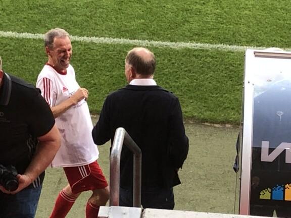 Zwei Menschen unterhalten sich. Der Linke Lacht und hat ein Fußballtrikot an.