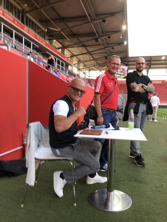 Eine Person sitzt an enem Tisch in einem Stadion und lacht in die Kamera. Zwei Menschen stehen dahinter.