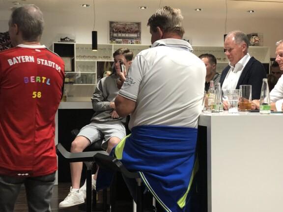 Stefan Reuther steht an einem Tisch. Auf dem Tisch stehen Gläser mit Getränken. Weitere fünf Personen sind zu sehen