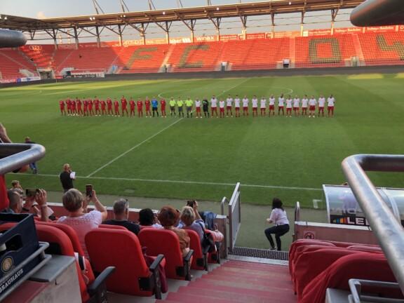 Zwei Fußballmannschaften stehen auf dem Spielfeld in einer Reihe. Im Vordergund sitzen Menschen auf der Tribüne.